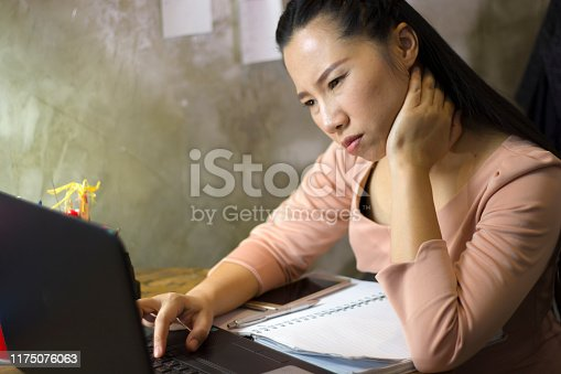 1049512672 istock photo Asian woman worker suffering from hurt,fatigue, pain at neck, muscle, stressed during working with laptop for a long time, 1175076063