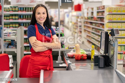 Attractive Asian woman working in supermarket standing at cash desk with arms crossed looking at camera smiling