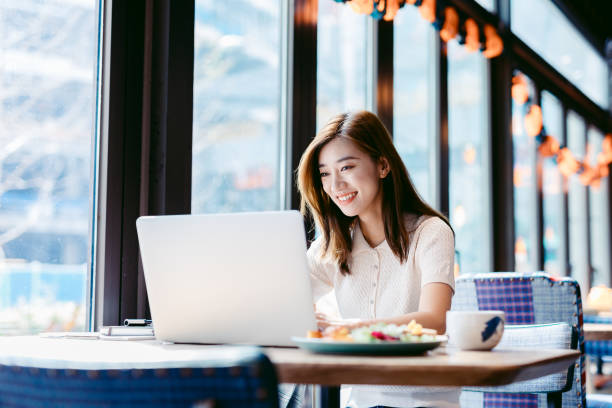 Asian woman working laptop at cafe. stock photo