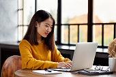自宅やカフェでラップトップで働くアジアの女性。明るい黄色のジャンパーの若い女性
