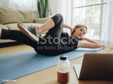Young asian woman exercise at home with the help of online tutorials in living room.