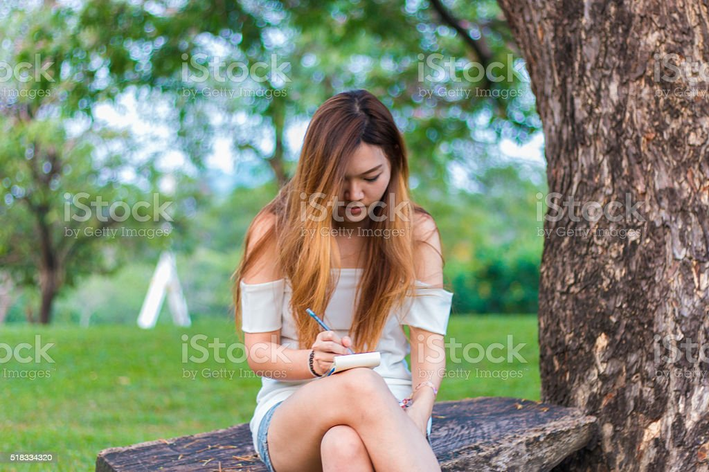 Asian woman writing on book at a garden or park stock photo