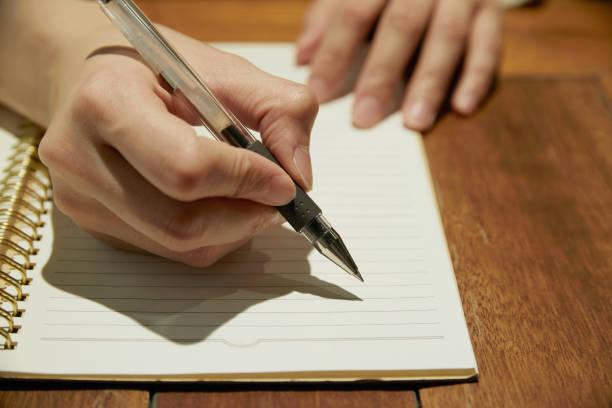 アジアの女性の本に書いて - ノート ストックフォトと画像