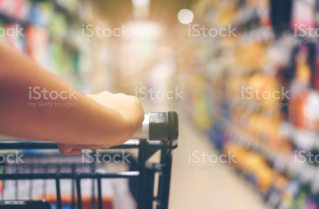 Asiatische Frau Hand mit Supermarkt, Trolley und viele Objekte, die der Hintergrund jedoch unscharf sind. – Foto