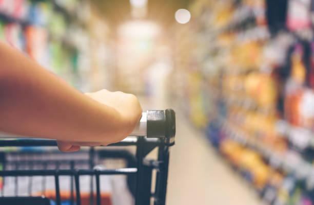 Main de la femme asiatique avec supermarché, trolley et beaucoup d'objets qui sont le fond flou. - Photo