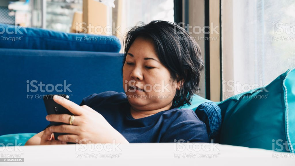 40 多歲的亞洲女性白色皮膚和豐滿的身體,穿著藍色衣服拿著智慧手機有懷疑,認為藍沙發上,靠近視窗的手勢圖像檔