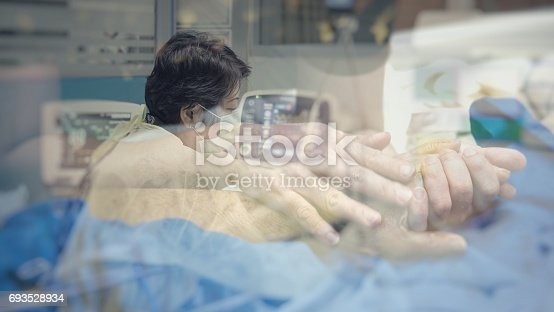 istock Asian women 40s years old in gown coat is a patient relative taking care of the CRE. or VRE. infected elder patient 80s years old on bed in the hospital. 693528934