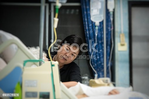 istock Asian women 40s years old is a patient relative taking care of the CRE. or VRE. infected elder patient 80s years old on bed in the hospital. 693528926