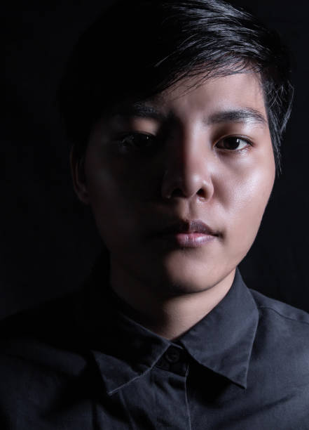 Asian women aged 20-29s Making the face look still with short hair wearing a blue shirt. Standing looking at the camera, single person photo. LGBTQ + concept Asian women aged 20-29s Making the face look still with short hair wearing a blue shirt. Standing looking at the camera, single person photo. LGBTQ + concept cisgender stock pictures, royalty-free photos & images