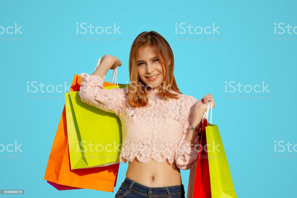 Asian women and Beautiful girl is holding shopping bags and using a smart phone and smiling while doing shopping stock photo