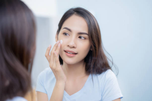 aziatische vrouwen toe te passen gezicht lotion. - crèmekleurig stockfoto's en -beelden