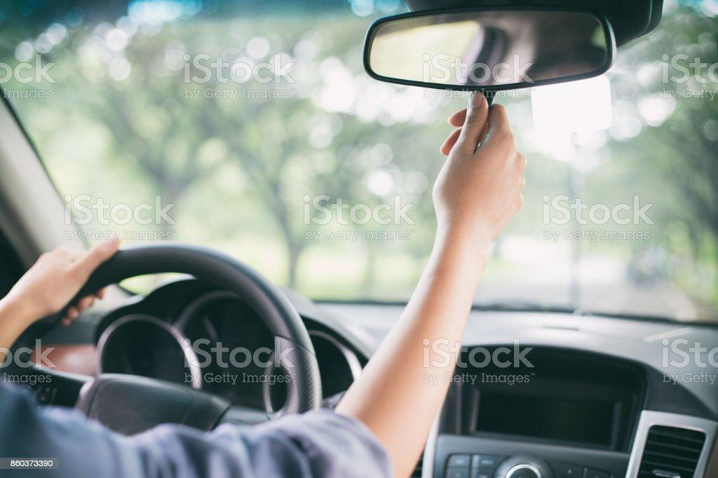 As mulheres asiáticas são ajustar o espelho retrovisor do carro - foto de acervo
