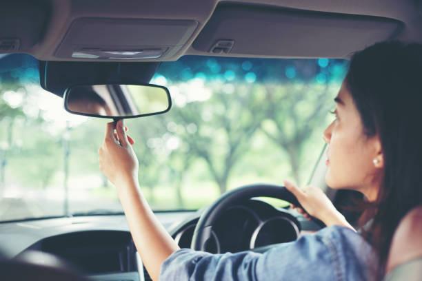 aziatische vrouwen zijn de achteruitkijkspiegel van de auto aanpassen - bijstellen stockfoto's en -beelden