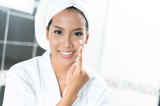 istock Asian women are applying cream and lotion to her face after bathing in the bathroom. 910314074
