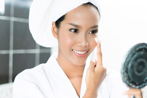 istock Asian women are applying cream and lotion to her face after bathing in the bathroom. 910314336