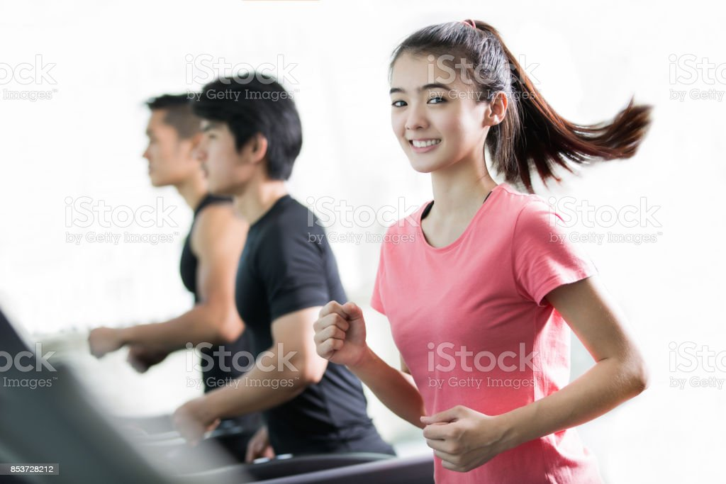 Asian women are exercising By running on a treadmill with her friends stock photo