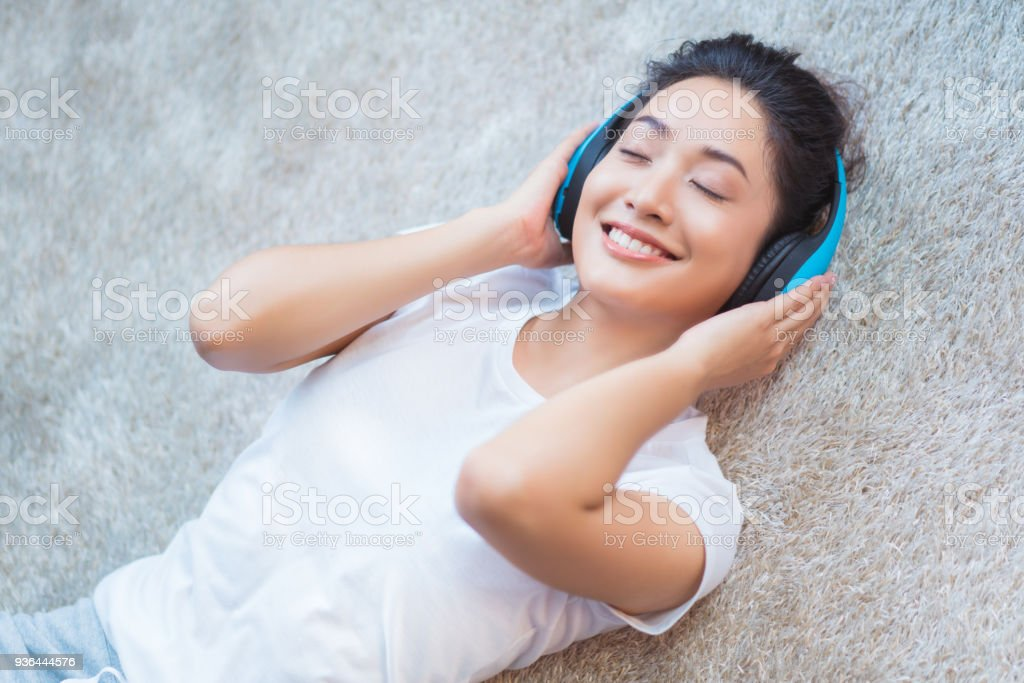 Asian women are listening to music and she sings in the room happily sleeping on the carpet stock photo