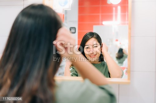 istock Asian women are looking herself reflection in mirror 1170200204