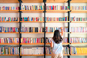 Asian women are picking up books on the bookshelf. To prepare to back to school