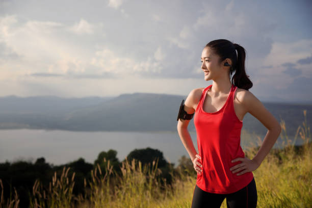 asian women are relaxing out of the running exercise. she is looking sun - carpet runner stock photos and pictures