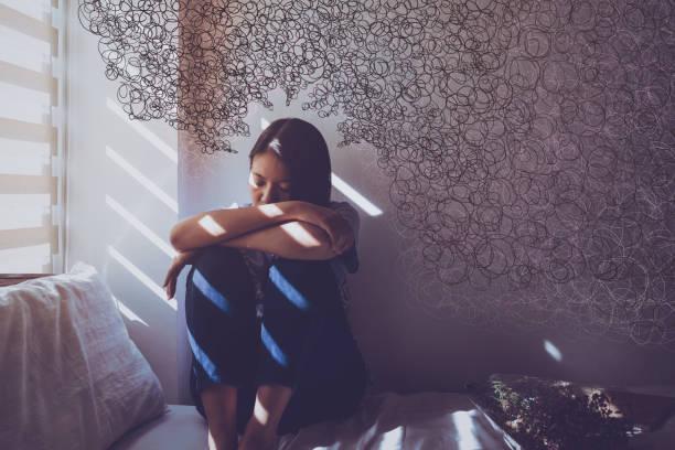 asiatische frauen sitzen umarmend im bett. traurig, enttäuscht und deprimiert im dunklen schlafzimmer und sonnenlicht aus dem fenster durch die jalousien mit freebiges tangel-drägtile-zeichnung. - besorgt stock-fotos und bilder