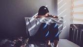 アジアの女性は、ベッドで自分の膝を抱いて座っています。悲しい気持ち、暗い寝室でブラインドを窓から日光愛の失望。ビンテージ トーン。