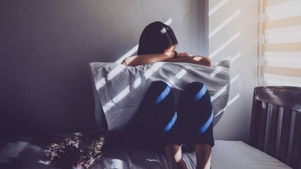 Asian women are sitting hugging their knees in bed. Feeling sad, disappointed in love In the dark bedroom and sunlight from the window through the blinds.Vintage tone. Asian women are sitting hugging their knees in bed. Feeling sad, disappointed in love In the dark bedroom and sunlight from the window through the blinds.Vintage tone. desolation stock pictures, royalty-free photos & images