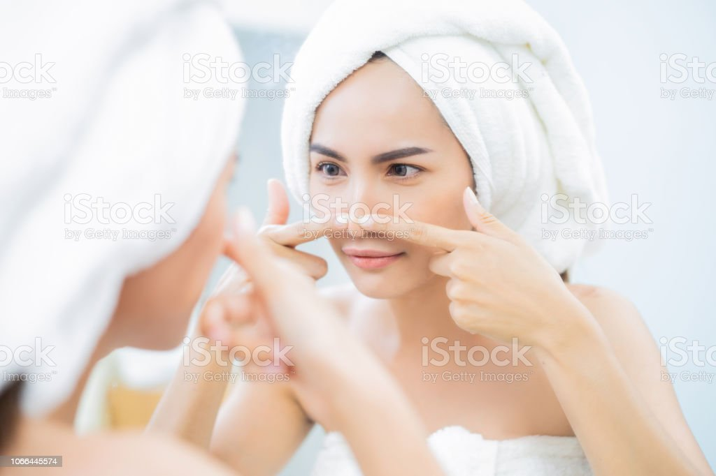 Asian women are squeezing acne after bathing. stock photo