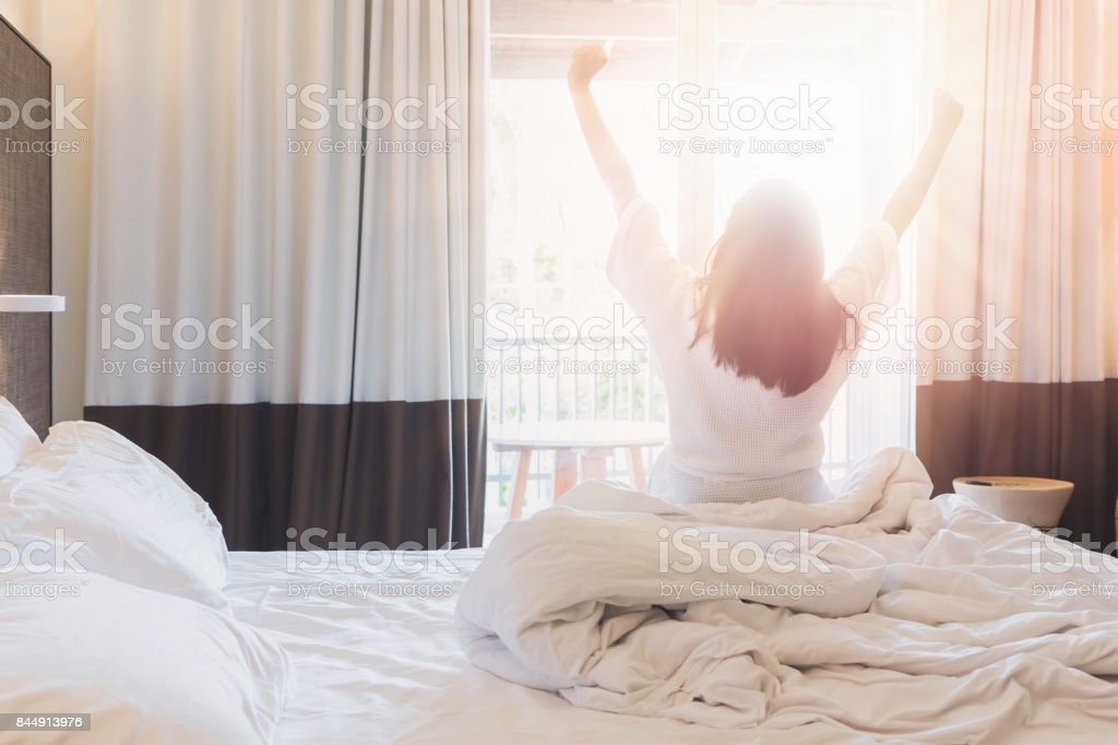 Asian women are staying in a hotel room after wake up on morning. Open the curtain in the room looking to outside view.Vintage tone. stock photo