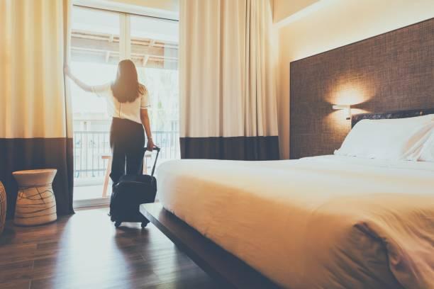 les femmes asiatiques séjournent dans une chambre d'hôtel. ouvrez le rideau dans la chambre avec le transport de bagages. le concept des gens est confortable pour voyager. - hôtel photos et images de collection