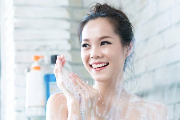 beautiful naked girl holding condom and smiling at camera