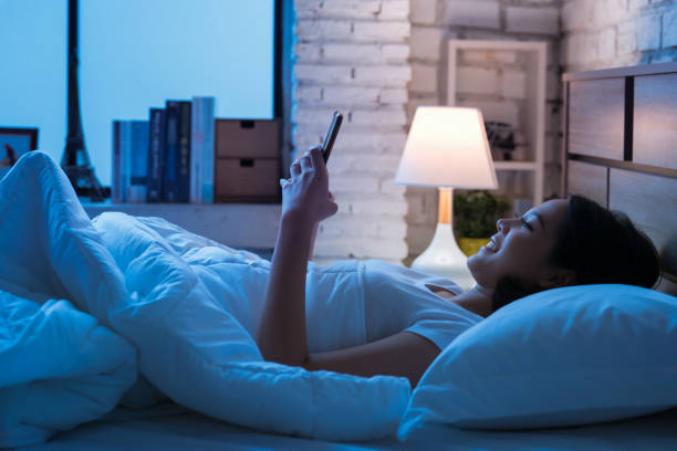 Asian women are using the smart phone on the bed before she sleeping at night. Mobile addict concept. stock photo