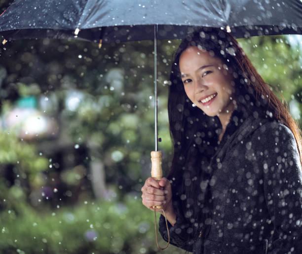 asiatische frauen sind mit sonnenschirmen, regen fällt - regenzeit stock-fotos und bilder
