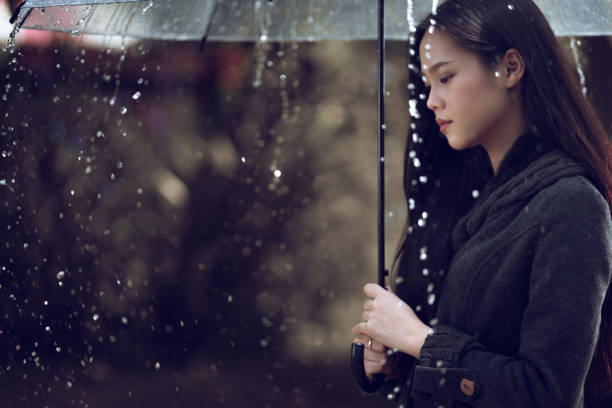 asian women are using umbrellas, rain is falling.focus blur - mockup outdoor rain foto e immagini stock