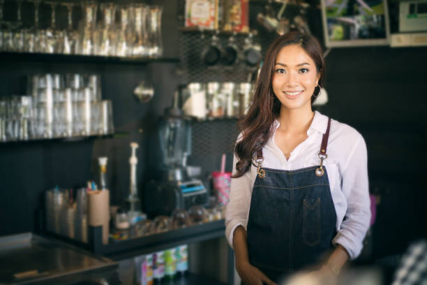 Asian women Barista smiling and using coffee machine in coffee shop counter - Working woman small business owner food and drink cafe concept stock photo