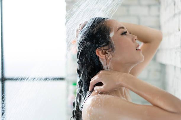 Asian women bathing and she was bathing and washing hair.she is happy stock photo