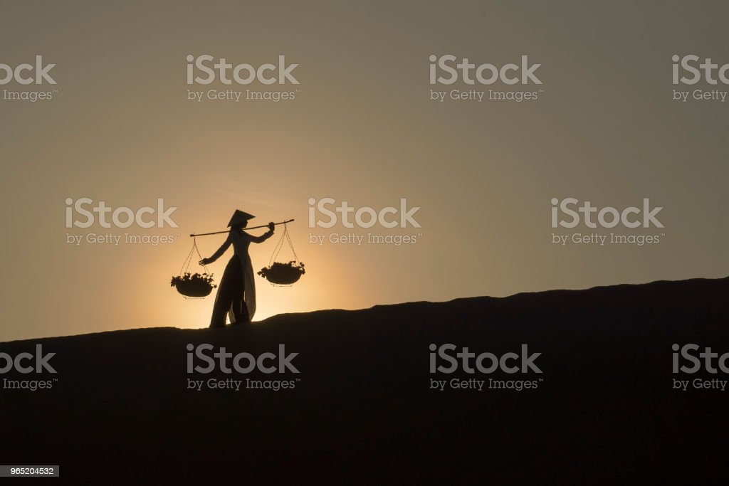 Asian women carrying baskets on her shoulders in the desert at sunset or sunrise time, Mui Ne, Vietnam.Asian women is walking and carry basket. royalty-free stock photo