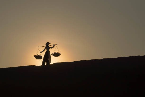 asian women carrying baskets on her shoulders in the desert at sunset or sunrise time, mui ne, vietnam.asian women is walking and carry basket. - ao dai stock photos and pictures