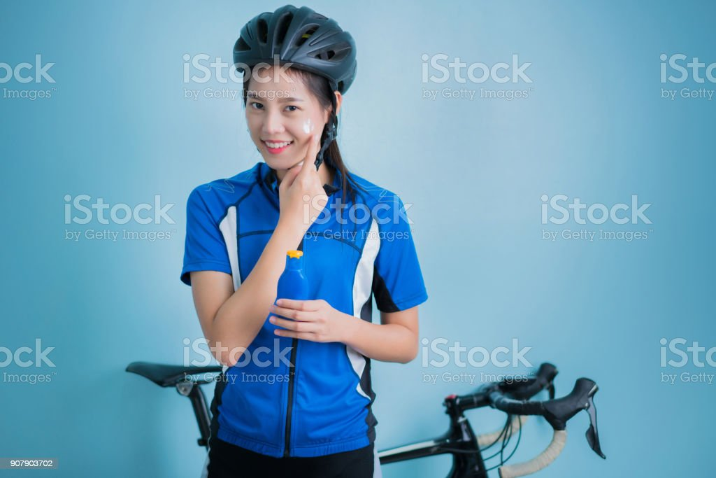 Asian women cyclists Applying sunscreen lotion on face stock photo