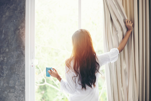 Asian women drinking coffee and wake up in her bed fully rested and open the curtains in the morning to get fresh air on sunshine