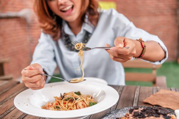 las mujeres asiáticas comiendo delicioso, se centran en la mano. - carbohidrato fotografías e imágenes de stock