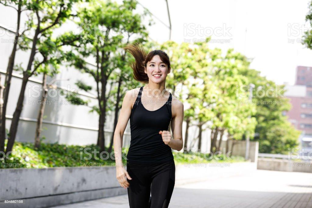 屋外ジョギングを楽しんでアジア女性 ストックフォト