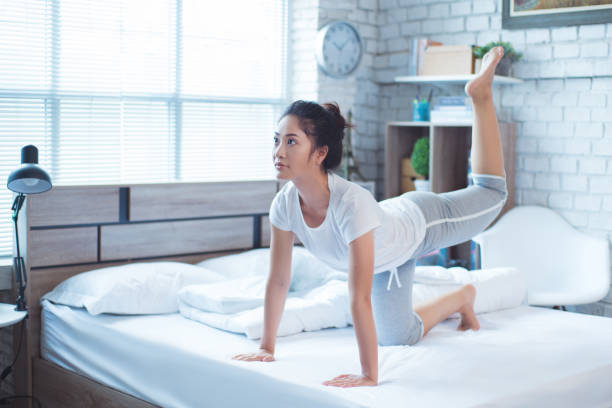 Asian women exercising in bed in the morning, she feels refreshed. stock photo