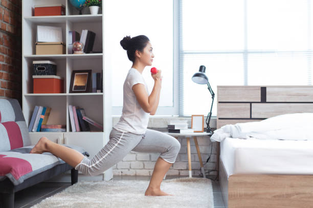 Asian women exercising in bed in the morning, she feels refreshed.She acts as squat. stock photo