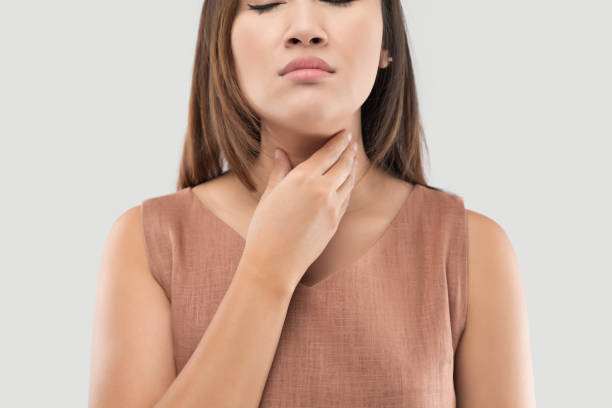 Asian women have symptoms of burning sensation on a gray background Asian women have symptoms of burning sensation on a gray background, Female with suffering from acid reflux or heartburn heartburn throat pain stock pictures, royalty-free photos & images