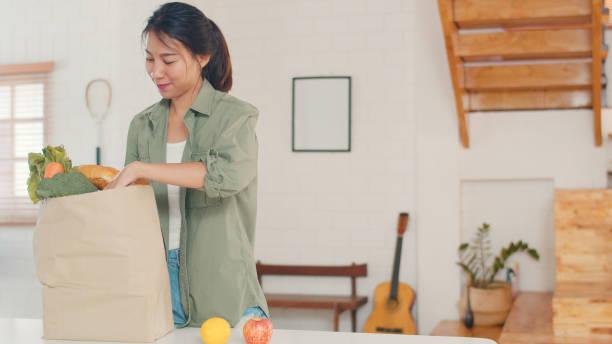 Asiatische Frauen halten Lebensmittel-Einkaufspapiertüten zu Hause, junge Asia Mädchen glücklich kaufen Gemüse und Obst gesunde und Bio-Produkt aus dem Supermarkt setzen es in der Küche in der Morgen-Konzept. – Foto
