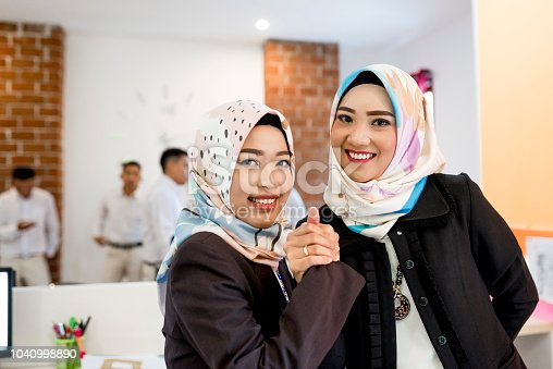 Two Indonesian women holding hands at office. They are wearing hijab.