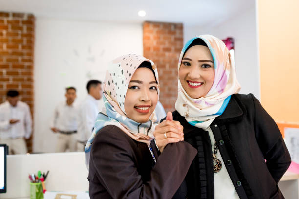 Asian women holding hands at office Two Indonesian women holding hands at office. They are wearing hijab. indonesian ethnicity stock pictures, royalty-free photos & images