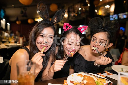 Asian women in halloween costume eating dinner at restaurant together