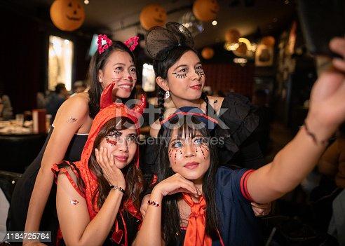 Asian women in Halloween costume taking group shot